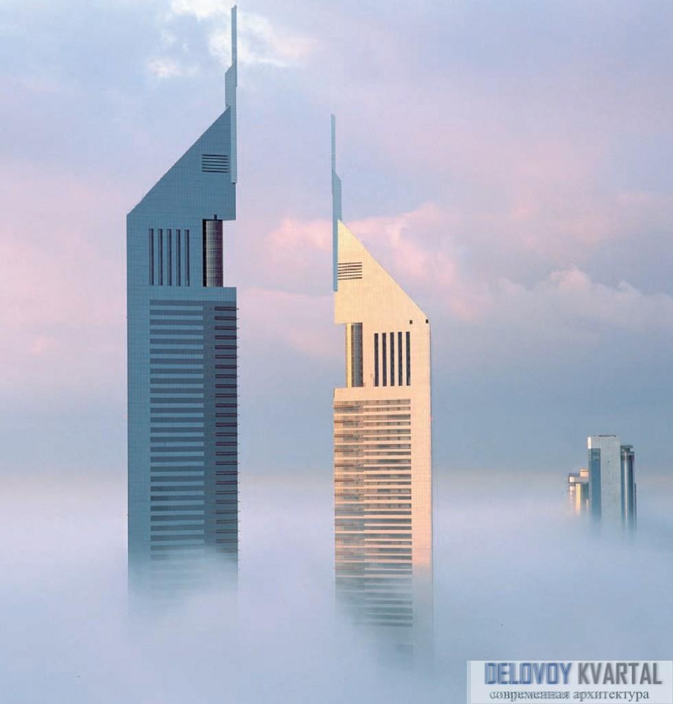 Небоскребы Emirates Towers возвышаются над затянутым утренним туманом Дубаем