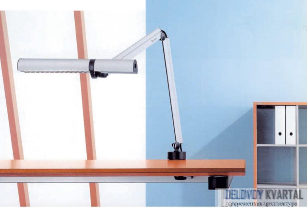 Вытянутый настольный светильник с креплением на кронштейне экономит место на столе и освещает обширную поверхность.