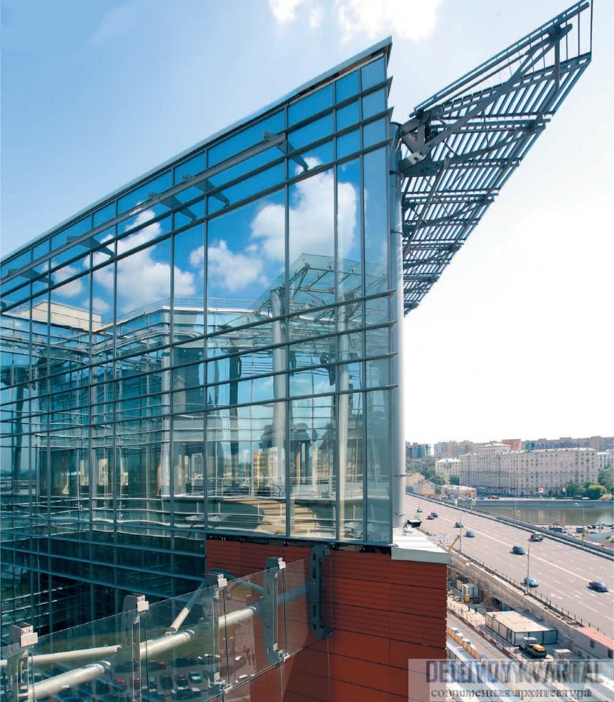 Угловой корпус, по замыслу архитекторов, получил своеобразную «корону», венчающую верхнюю стеклянную часть здания и защищающую ее от осад