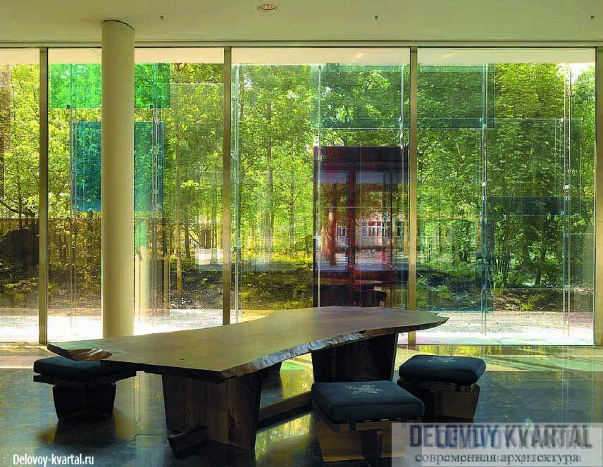 Фрагмент вестибюля. Его стеклянные стены опускаются до самой земли и почти незаметны на фоне густой листвы парка