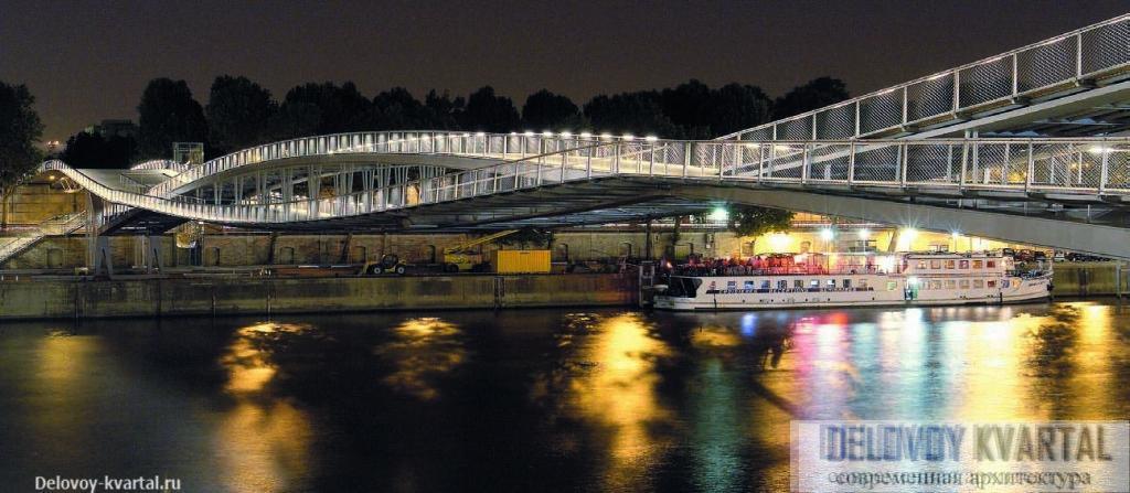 Ночью пешеходный мост Симоны де Бовуар эффектно подсвечивается, и его сходство с линзой еще более очевидно