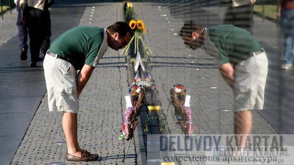 Посетители смотрят на имена погибших и в отражении видят самих себя