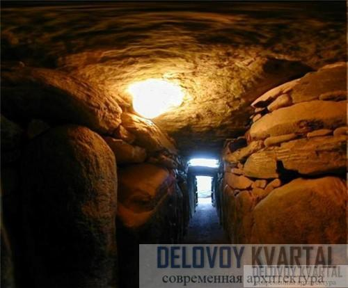 Коридор идет под холм, по бокам его стоят камни-подпорки, многие из которых украшены резьбой